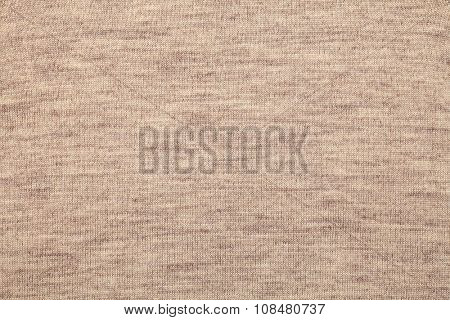 Real beige knitted fabric made of heathered yarn textured background