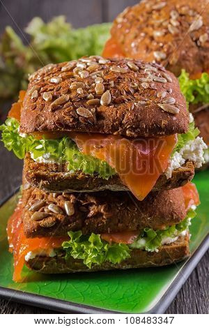 Sandwich With Whole Grain Bread And Salmon On Rustic Wooden Background