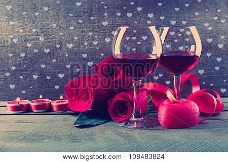 Composition with red wine in glasses, red roses and candles on dark festive background