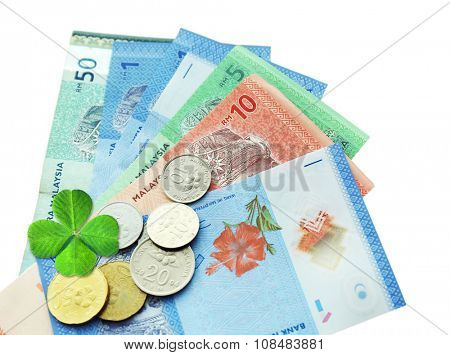 Money banknotes and coins with clover leaf isolated on white