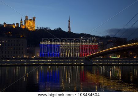 LYON-FRANCE NOVEMBER 17, 2015:  The historic courthouse of Lyon with the colors of France flag with  Basilica of Fourviere over the soane in background at sunset.