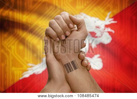 Barcode Id Number On Wrist Of Dark Skinned Person And National Flag On Background - Bhutan