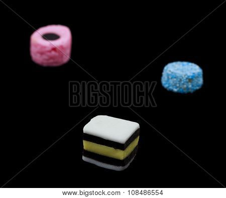 Three liquorice allsorts candy isolated on black background