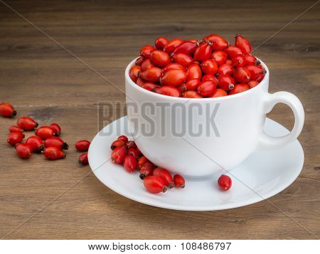White mug filled with briar fruit on wooden surface