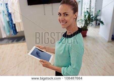 Happy female seller using digital tablet during work in shop