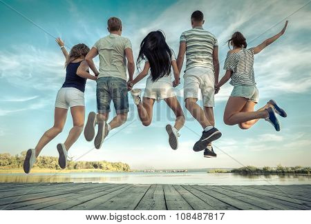 Group of friends jumping on the pier under sunlight.