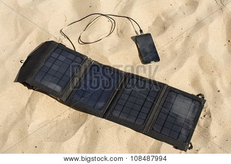 Portable Solar Panel Is On The Beach Charges Mobile Phone.