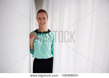 Portrait of a happy charming woman seller posing while standing in modern interior
