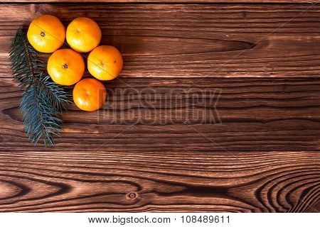 Christmas and New Year Mandarins next to the Christmas tree branches with cones on a wooden backgrou