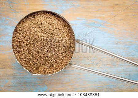 organic noni fruit powder in a metal measuring scoop against painted wood