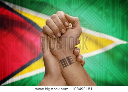 Barcode Id Number On Wrist Of Dark Skinned Person And National Flag On Background - Guyana