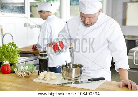 Two professional chefs preparing food in large kitchen