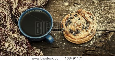 Coffee cup, scarf and sweet bun  on a wooden background.