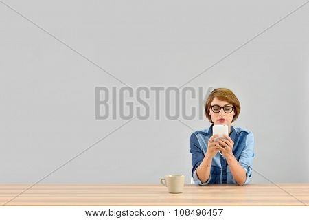 Young woman sitting at desk sending message on smartphone