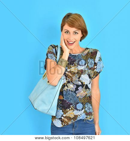 Beautiful girl with purse standing on blue background