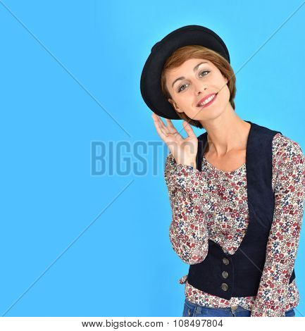 Trendy girl with black hat standing on blue background