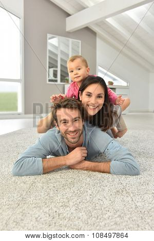 Parents and baby girl laying on carpet,