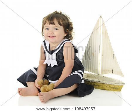 An adorable baby sailor girl happily sitting with her toy sailboat behind her.  On a white background.