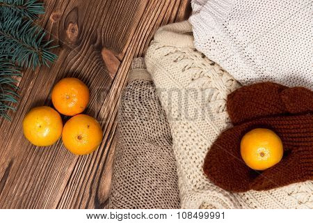 Christmas and New Year Mandarins next to the colorful knitted sweaters, cones, branches of the Chris