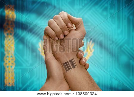 Barcode Id Number On Wrist Of Dark Skinned Person And National Flag On Background - Kazakhstan
