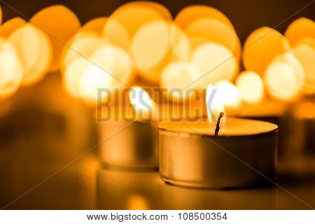Christmas candles burning at night. Abstract candles background. Golden light of cand