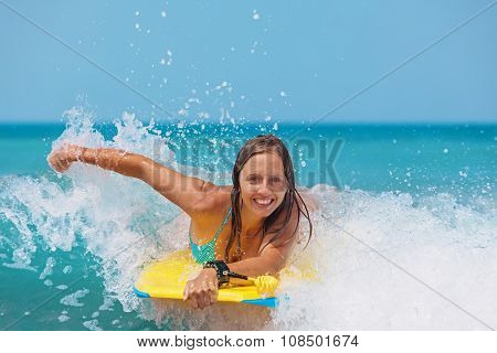 Joyful Girl Swimming With Boogie Board On The Sea Waves