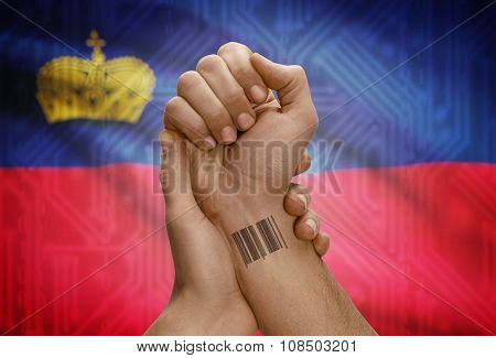 Barcode Id Number On Wrist Of Dark Skinned Person And National Flag On Background - Liechtenstein