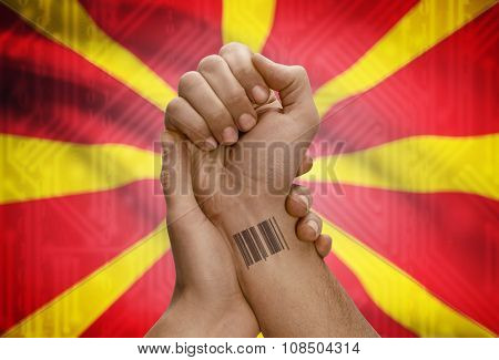 Barcode Id Number On Wrist Of Dark Skinned Person And National Flag On Background - Macedonia