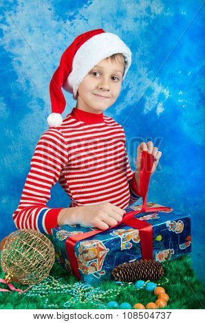 Smiling Boy In Santa Hat Tieing Red Ribbon On Box