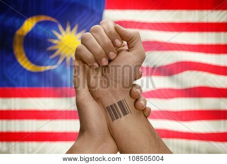 Barcode Id Number On Wrist Of Dark Skinned Person And National Flag On Background - Malaysia