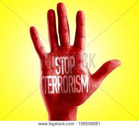Stop Terrorism painted on hand with yellow background