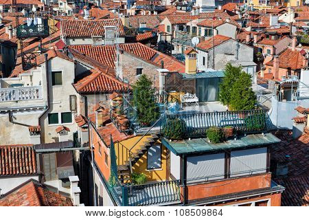 Aerial cityscape view over the rooftops and historic buildings of Venice, Italy with blue sky