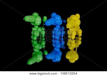 Three Colorful Balloon Dog Poodles On A Mirror