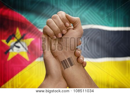 Barcode Id Number On Wrist Of Dark Skinned Person And National Flag On Background - Mozambique