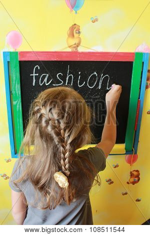 Girl With Nice Plaits Writes Fashion On Blackboard