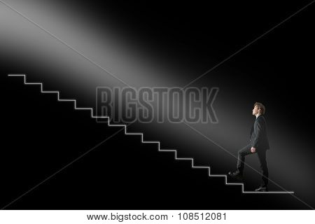 Businessman Walking Upwards Towards The Light On Conceptual Stairway Over Black Background