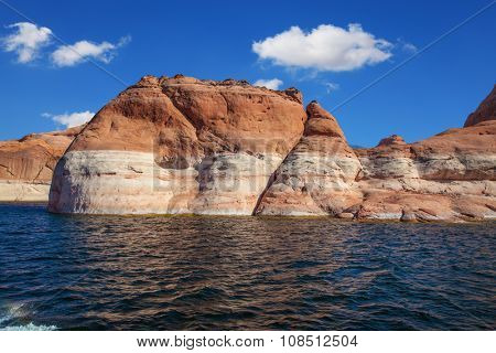 Picturesque artificial huge reservoir Powell on the river Colorado, USA. The lake is surrounded with picturesque coast from orange sandstone. Walk on the lake Powell on a sunset