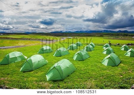 Campground in Iceland. Green tent on a grassy lawn.