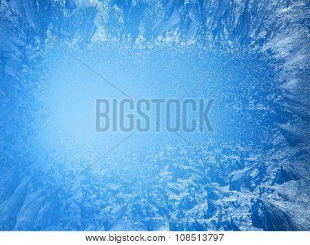 Frosty patterns on the edge of a frozen window.