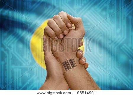 Barcode Id Number On Wrist Of Dark Skinned Person And National Flag On Background - Palau