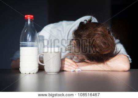 Tired woman with head on the table. Health issue, hangover or Monday morning concept.