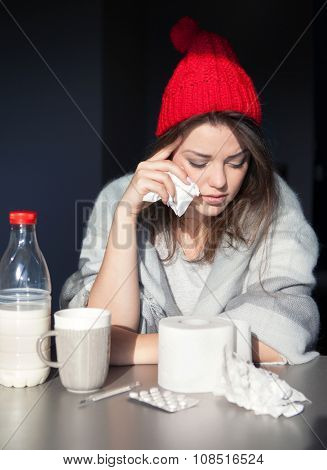 Unhappy woman wearing knitted hat and wrapped in blanket. Tissue paper and pills on the table. Health issue, cold, flue, fever, runny nose concept.