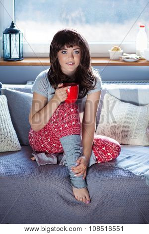 Young beautiful woman sitting home on the couch wearing Christmas print pajamas holding cup of coffee
