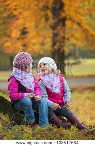 Two children sitting in a park on a tree trunk