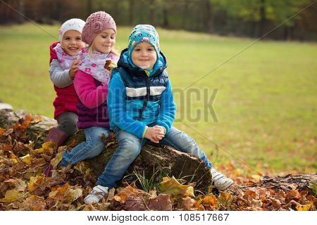 Three children sitting in a park on a tree trunk