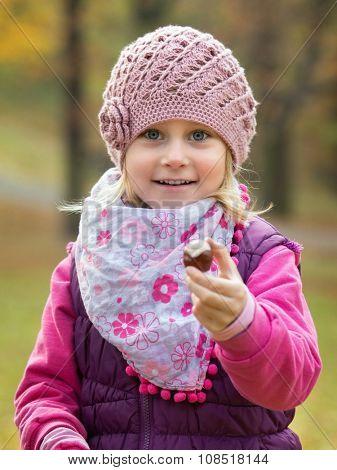 Portrait little girl in autumn park hold in hand chestnut