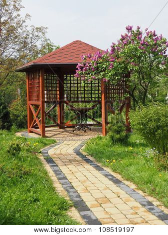 Arbor in garden with lilac vertical
