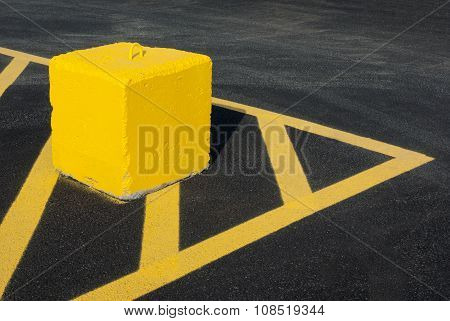 yellow concrete block pointing lines asphalt