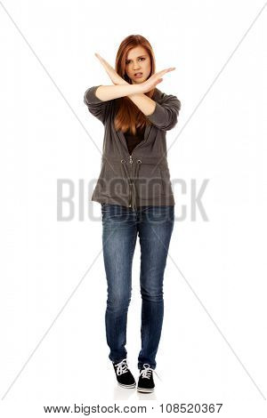 Teenage woman making stop sign with crossed hands.