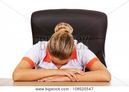 Tired young female doctoror nurse sleeping on the desk.
